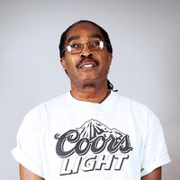 Studio portrait of Ainsley, a member of Elimu Carnival Band. He is wearing a white T-shirt with a Coors logo.