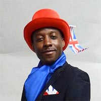 Studio portrait of Anthony, a member of Elimu Carnival Band. He is wearing a dark blue jacket and blue silk scarf and a red hat decorated with a Union Jack.