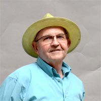 Studio portrait of Barry, a member of Elimu Carnival Band. He is wearing a blue shirt, khaki trousers and a straw hat.