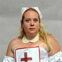 Studio portrait of Brigitta, a member of Elimu Carnival Band. She is wearing the costume of a nurse.