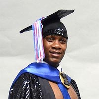 Studio portrait of Carney, a member of Elimu Carnival Band. He is wearing a black mortar board and a black cloak. There is a bright blue sash around his neck.