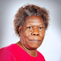 Studio portrait of Cheryl, a member of Elimu Carnival Band. She is wearing a red T-shirt with a black rhino logo on the front.