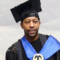 Studio portrait of Cyril, a member of Elimu Carnival Band. He is wearing a black mortar board and a black cloak and T-shirt. There is a bright blue sash around his neck.