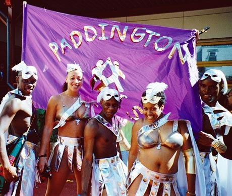 Photograph of carnival dancers in silver costumes posing in front of a purple banner with 'Paddington Arts' depicted in silver lettering.