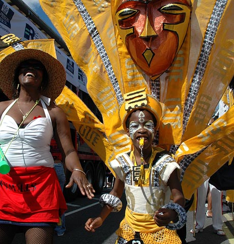 Photograph of boy carnival dancer in yellow costume, whistle in mouth, above him are large yellow wings and a tribal mask. He is accompanied by a woman in white T-shirt and straw hat, also dancing.