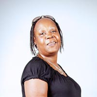 Studio portrait of Frances, a member of Elimu Carnival Band. She is wearing a black top over blue jeans and sandals.