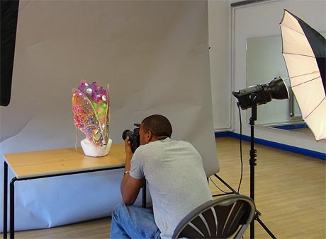 Photograph of man taking a picture of a carnival headdress in a makeshift studio set.