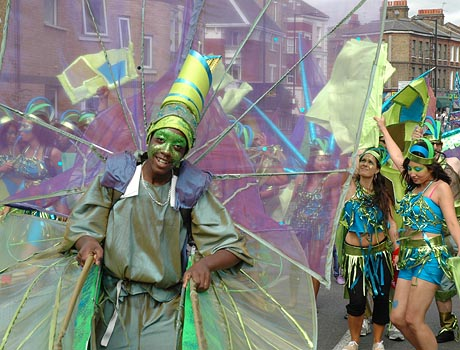 Photograph of carnival dancer in green costume with headdress and wings, followed by two dancers in blue costumes.
