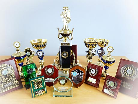 Photograph of table laden with trophies, cups, plaques and other awards.