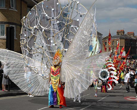 Photo of the Carnival King wearing a multi-coloured costume that includes huge white wings spread either side and a circular motif towering above him.
