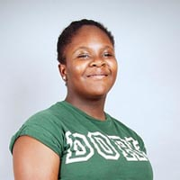 Studio portrait of Lauryn, a member of Elimu Carnival Band. She is wearing a green T-shirt.