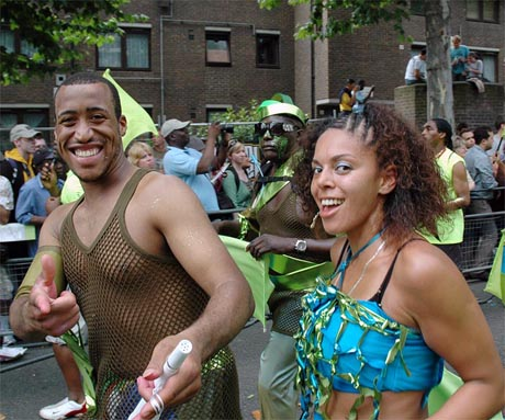Photo showing two dancers, a man in a green vest pointing at the camera and girl in a blue costume smiling at the photographer.