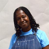 Yvonne wearing blue denim dungarees over a pale blue T-shirt