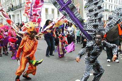 Photo of Notting Hill Carnival featuring two boys, each with a cotume and backpack supporting large wings, one coloured orange and red, the other black and white.