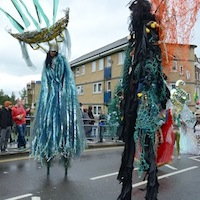 Three dancers on 10 feet high stilts dressed in long flowing costumes and elaborate head pieces