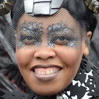 Dancer's face made up with intricate desugns and ornate collar and wig with two rosettes on each side and black veil.