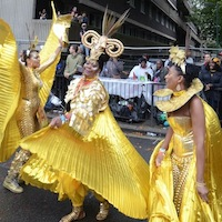 Three dancers with elaborate gold shimmering costumes including extended wings and ornate head dresses.