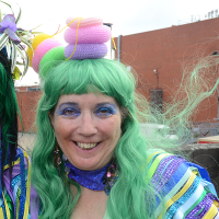 Photo of woman in costume decorated with ribbons and wearing long green wig and headdress