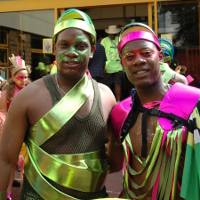 Photo of two male dancers in green and red costumes standing in front of Paddington Arts building.