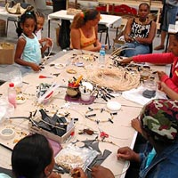 A group of young girls seated around a table upon which are hoops and beads and glue, tape, scissors and other things for making decorations