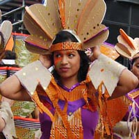 Latin American inspired costume coloured in orange, purple and cream with conspicuous headdresses.