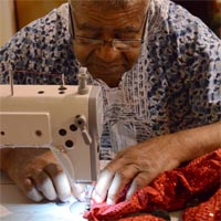 Man sewing new outfits out of a sparkling red fabric on a sewing machine for the upcoming carnival.