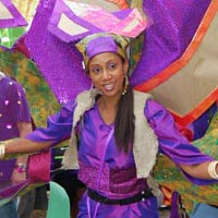 Woman dressed in purple with a giant semicircular construction, out of various colours and farbics, on her back.