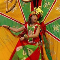 Girl dancer wearing red and green costume with very large yellow and green patterned wings on a backpack