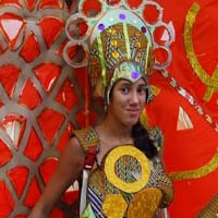 Woman, dressed in a hauberk with circles on it and a big impressiv headdress. She has a giant red disk on her back, decorated with golden and silver symbols.