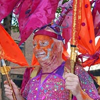 Man, dressed in purple, with a purple and orange construction above his head.