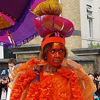 Woman in a orange dress with a extraordinary colourful headdress out of three smaller umbrellas and one really big upside down one.