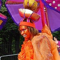 Side view of a woman in a orange dress with a extraordinary colourful headdress out of three smaller umbrellas and one really big upside down one.