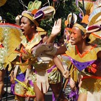 Members of Elimu dressed in latin american native inspired orange and purple outfits, as a part of the carnival parade.