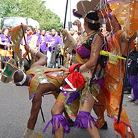 Members of Elimu performing a dance cheography during the carnival. The members wear latin american native inspired outfits.
