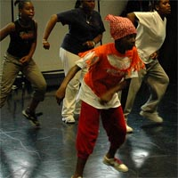Eldora with several children working on their choreography for Notting Hill Carnival