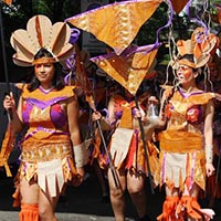 Members of Elimu dressed in latin american native inspired orange, partly cream and purple, outfits, as a part of the carnival parade.