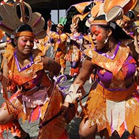 Members of Elimu dressed in latin american native inspired orange partly creme and purple outfits, dancing in the street.