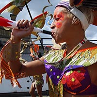 Member of Elimu blowing the horn as a part of the carnival performance.