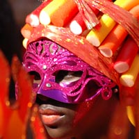 A girl wears a purple decorated mask and a headdress of red, orange and yellow tubes