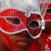A girl wears a red sequinned mask decorated with long silver strands pointing upwards