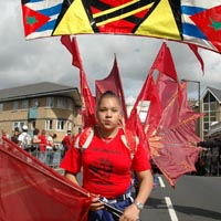A girl wearing a backpack supporting a banner comprising the flags of many Caribbean countries