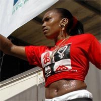 Eldora with red T-shirt and white trousers dancing at Notting Hill Carnival