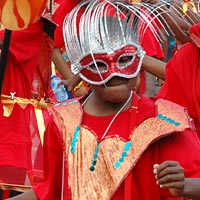 Girls in carnival parade, dancing in red costumes with hoop skirts and wearing red sequinned masks decorated with long silver strands pointing upwards