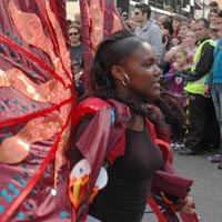 Girl in black wearing a backpack that supports two large wings of dark red fabric decorated with coloured spots