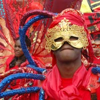 Boy in red costume decorated with long pipes of blue and red, he is and wearing a gold mask