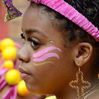 Close-up of a woman with a pink headdress, a golden cross earring and pink face-painting.