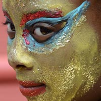 Close-up of a golden Face-painting with blue and red details around the eyes and a golden snood.