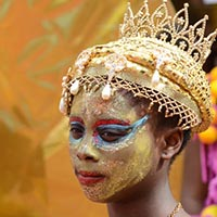 Young Woman with a golden face, a golden snood and a crown above her head.