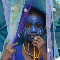 A girl with her face painted blue, dressed in blue and got a giant blue hat with various fabrics, such as lace, above her head.