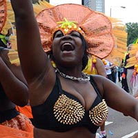woman wearing a black bra with golden spikes on it and a orange skirt and headdress.